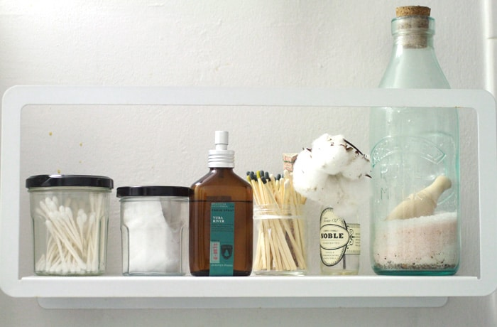 Bathroom shelf with room spray, cotton balls, bath salts