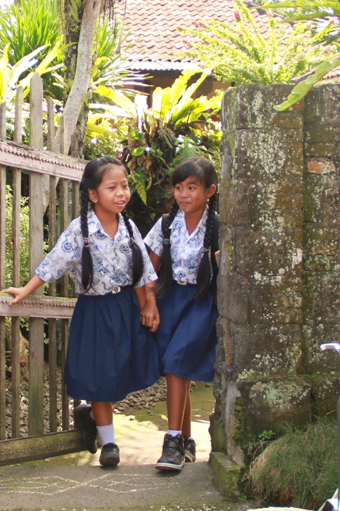 Two school girls giggled and shyly watched our group of cyclists during the bike tour of the Ubud countryside