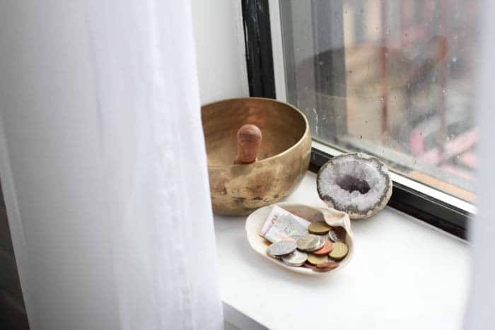 Little things on a window sill: a Tibetan singing bowl, a shell filled with foreign currency collected on my travels, and a geode I have from a childhood road trip with my grandparents.