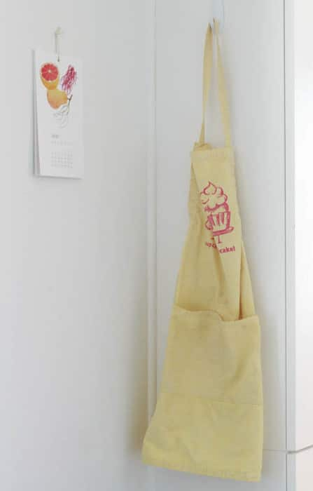 A Buy Local calendar and locally-printed apron hang behind the pantry.