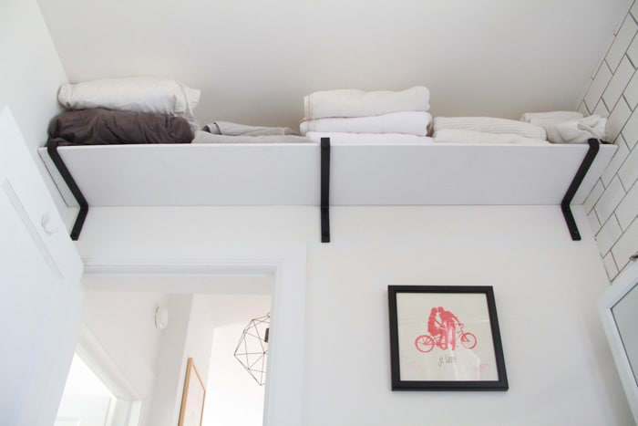 A shelf goes above the bathroom door for extra storage.