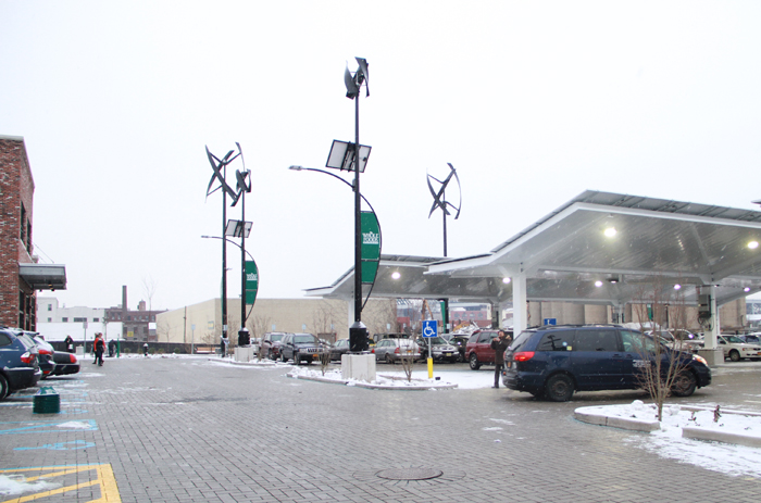The parking lot has windmills and solar arrays to power the electric vehicle charging stations.