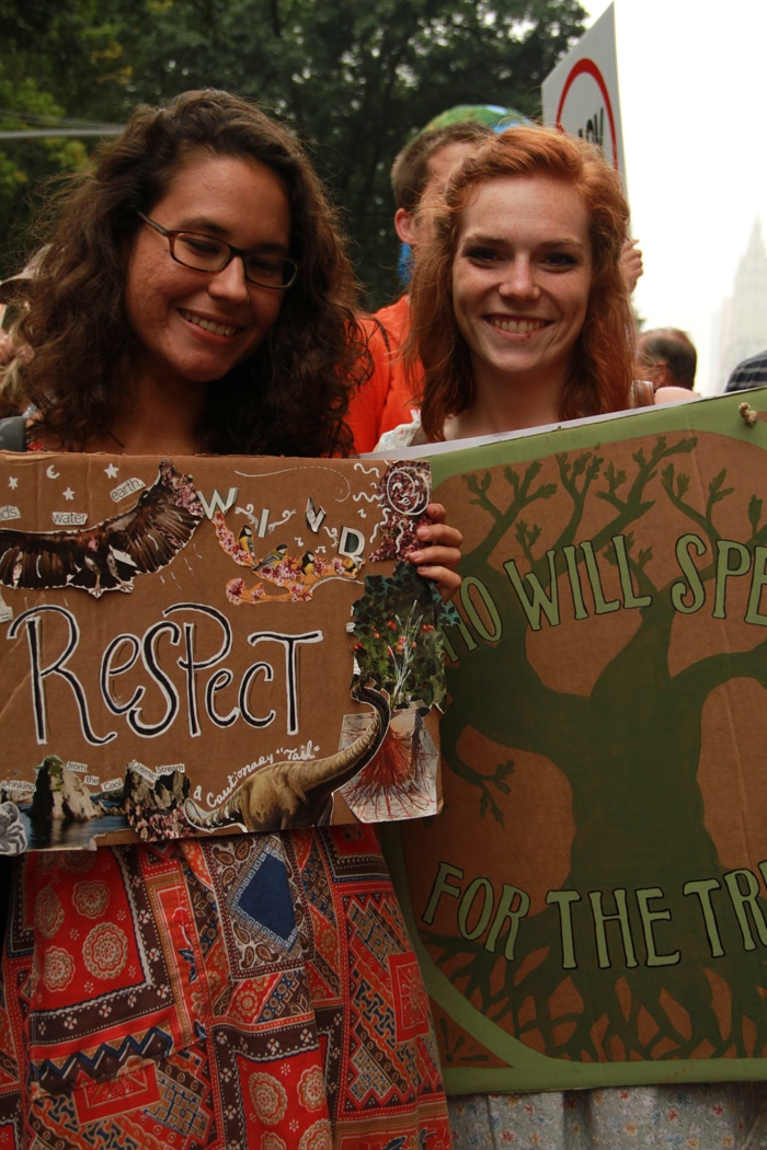 Women holding hand-drawn signs in the Climate March