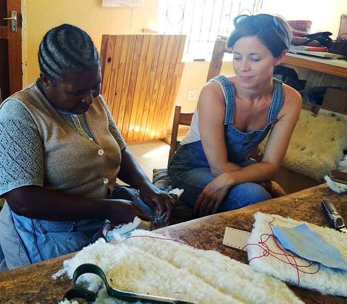Harper Poe of Proud Mary in Lesotho, watching an artisan make recycled denim booties.