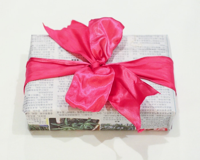 Eco-friendly gift wrap idea: use an old newspaper, or buy a foreign language newspaper for more flair