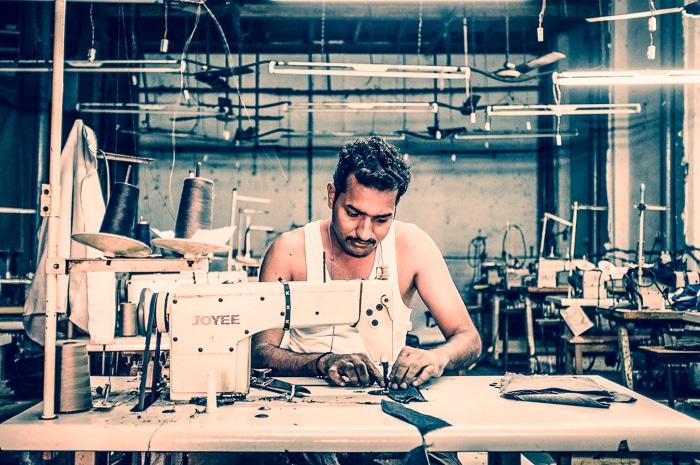 MUMBAI, INDIA - 12 JANUARY 2015: Indian worker sews in clothing factory in Dharavi slum.