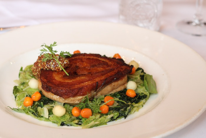 Locally sourced entrée of braised pork belly roulade