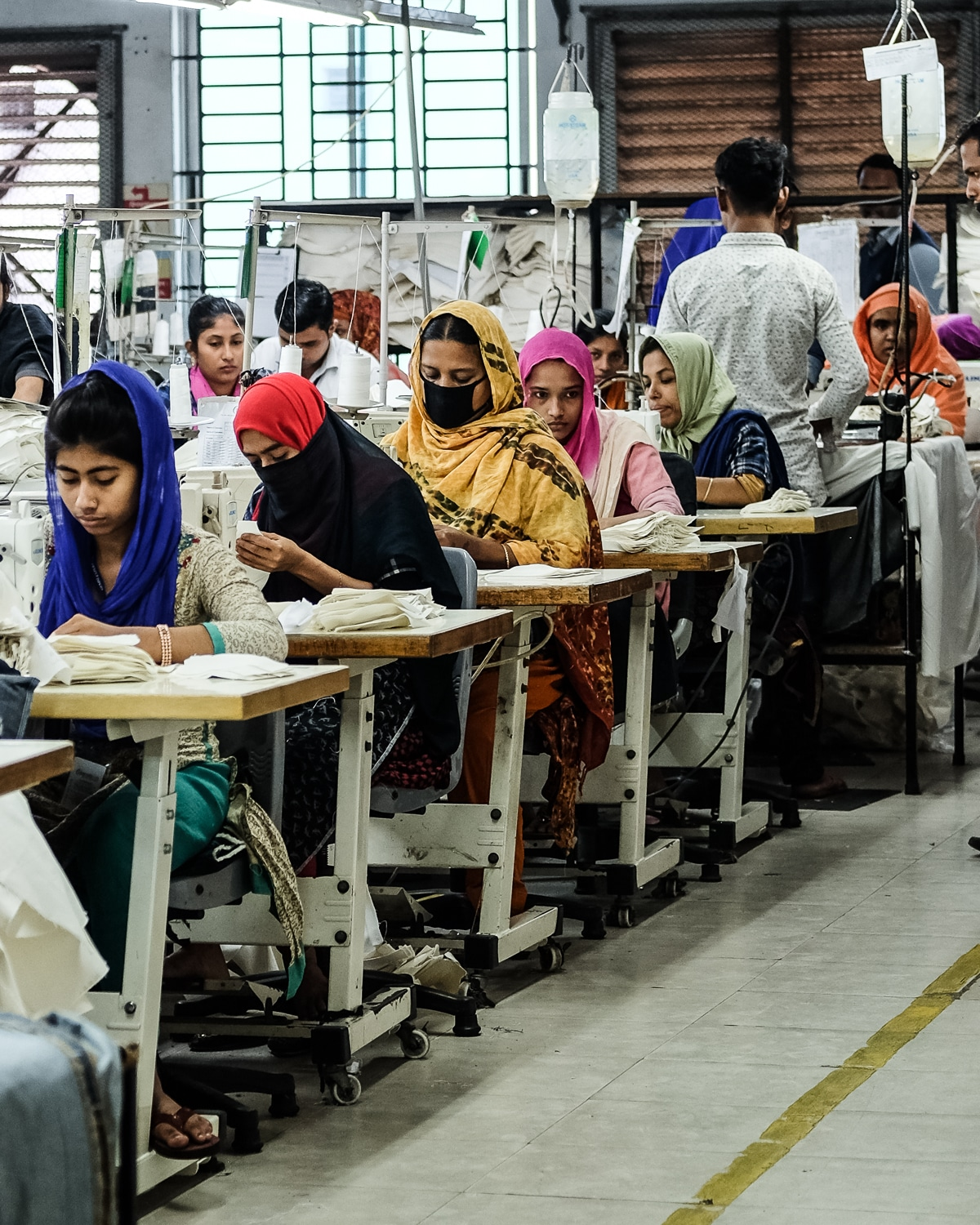 A row of female garment workers wearing face masks
