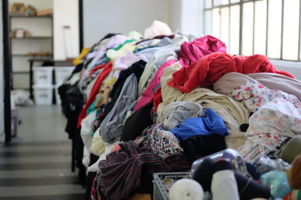 Piles of colorful used clothing overflow from bins at the Fabscrap sorting facility in Brooklyn.