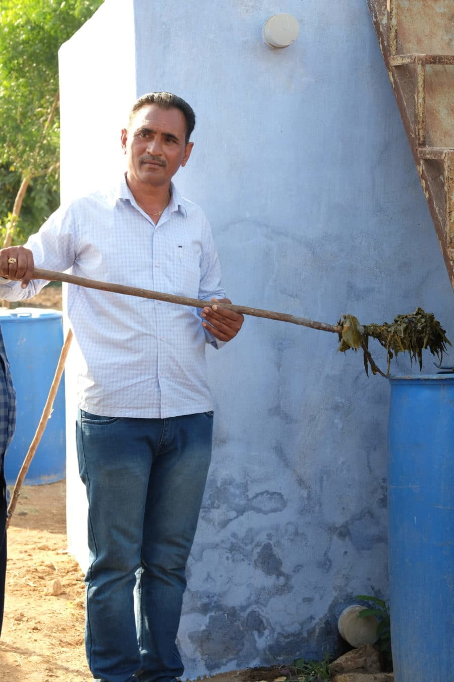 An Indian farmer holds a paddle with organic inputs.